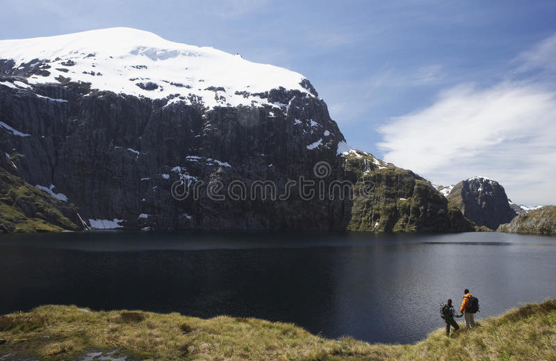 Two Hikers Looking At Mountain Lake Royalty Free Stock Photos