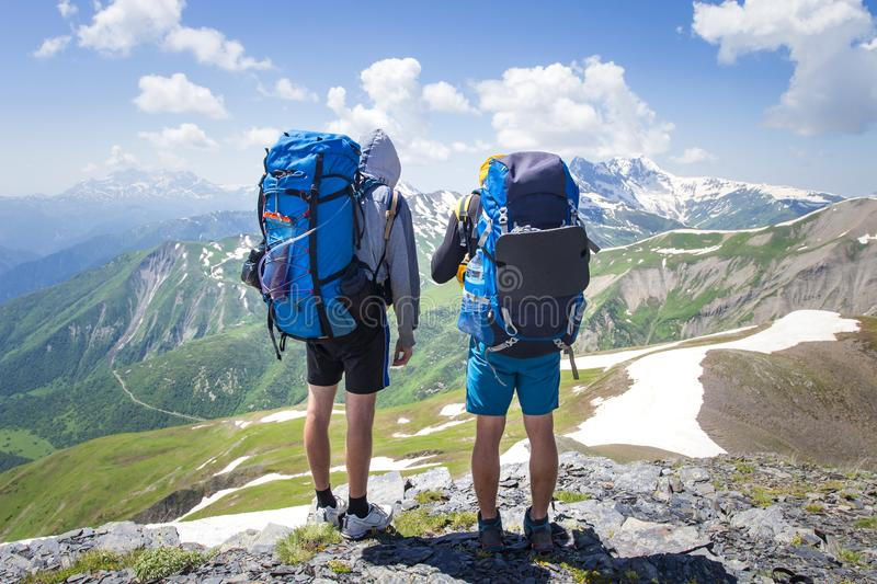 Two hikers in mountains with backpacks on sunny summer day. Mountain trek in Svaneti, Georgia royalty free stock photography