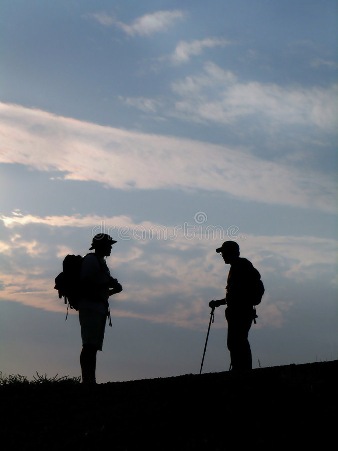 Two Hikers Silhouette. Silhouette of two hikers on the summit of a peak with sky in background stock photo