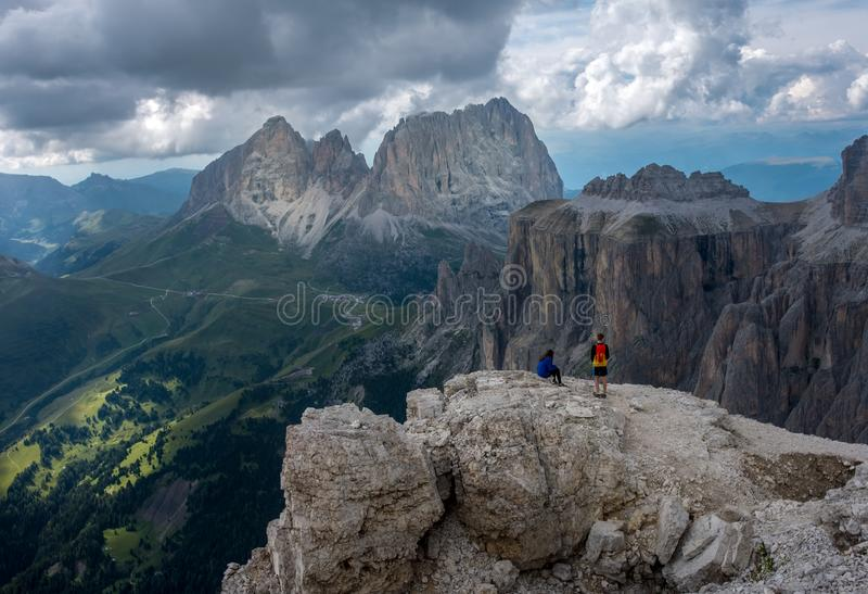 Two hikers taking a rest on top of Sass Pordoi in the Italian Dolomite mountains stock image