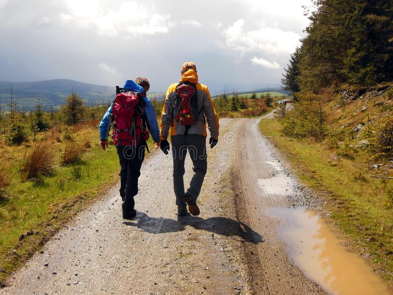 Hiking Back Trails of Ireland. Two hikers trudge along a muddy trail after a rainstorm in County Wicklow Ireland on route to historic Glendalough royalty free stock photo