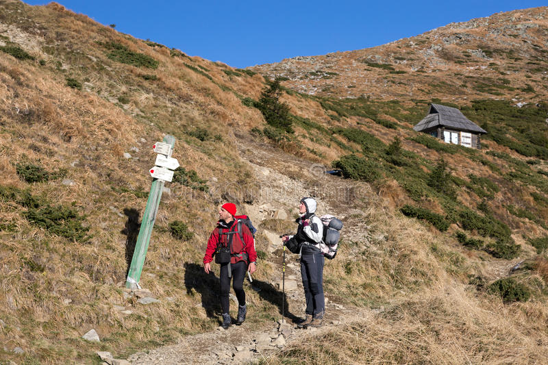 Two Hikers walking on Mountain grassy slope looking Trail Sign stock image