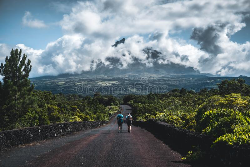 Two hikers walking on a narrow road surrounded with greenery with cloudy mountain in the background stock images