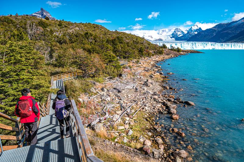 Two hikers and walking path at Lago Argentino near huge Perito Moreno glacier in Patagonia in golden Autumn, South America. Sunny day, blue sky stock photos