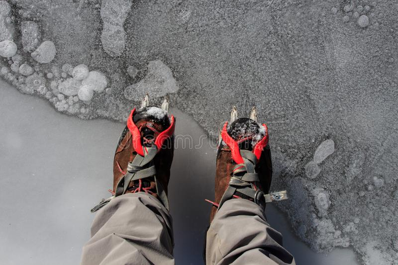 Two hiking boots with crampons on the ice. Mountain sport accessories concept royalty free stock image