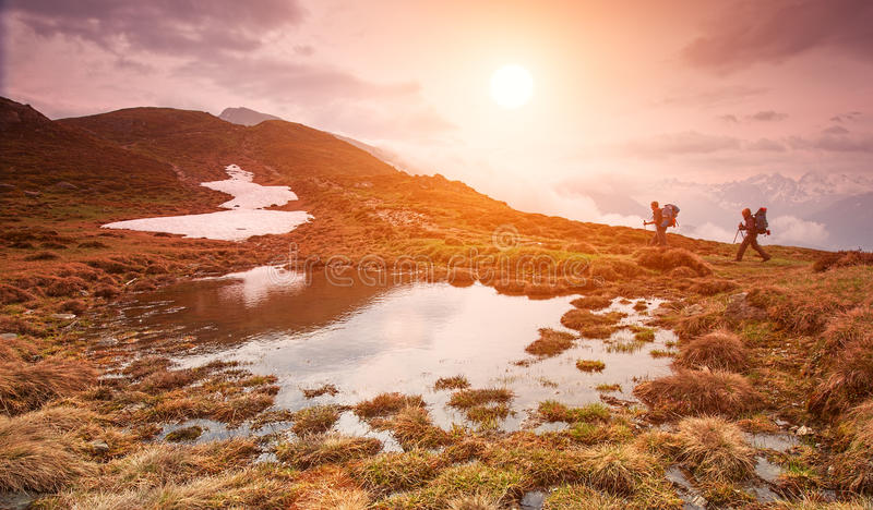 Two hiking in the mountains in beautiful morning at a small lake royalty free stock image