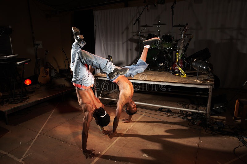 Two hip-hop dancers. Two freestyle hip-hop dancers in a dancing training session. Two young adult males in a home training studio with stage and instruments. Lit stock photography