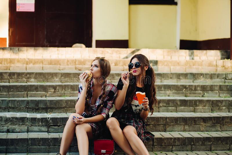 Two hipster girls sitting on stairs and eating fast food. stock images