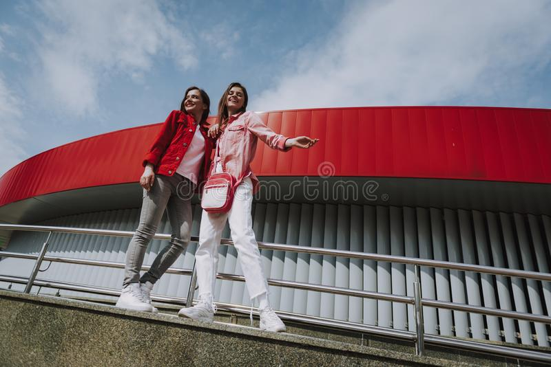 Two hipster girls on city ramp parapet. Urban lifestyle concept. Full length low angle portrait of young happy hipster ladies enjoying time together while stock photography
