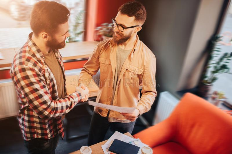 Two hipsters that wear casual clothes standing in a slall cafe and shaking their hands.One of them is holdnig a document stock photos
