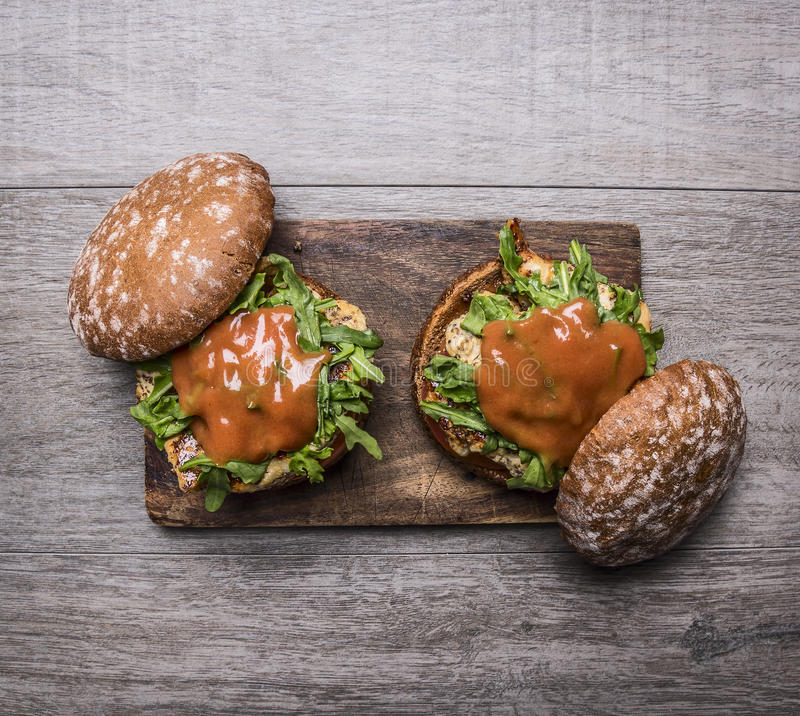Two home burgers with chicken in mustard sauce, arugula, tomatoes on a cutting board on wooden rustic background top view close up. Two home burgers chicken in stock image