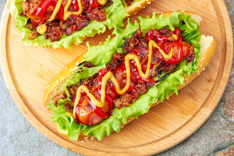 Two homemade hot dogs with lettuce, bacon and onion toppings stock image