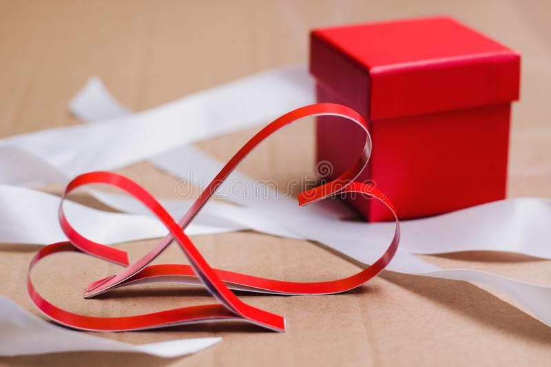 Two homemade paper red hearts and red gift box with white ribbons. Valentine`s day and love symbol royalty free stock photo