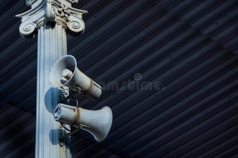 Two horn load speaker on antique column metal frame under roofing. Industrial or transport announcement information system. Old. Weathered style devices with stock photography