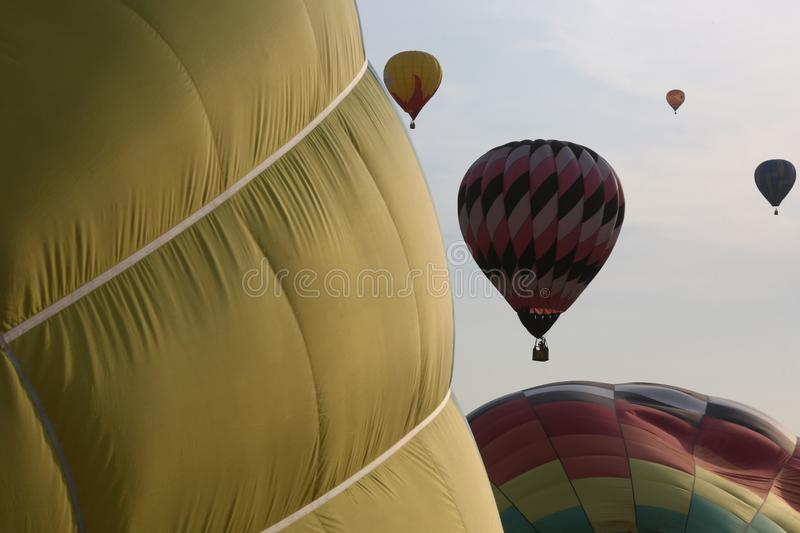 Two hot air balloons inflate side-by-side as four more fly in the background royalty free stock photo