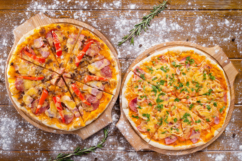 Two hot beautiful delicious Italian pizza with bacon cheese and vegetables stock images