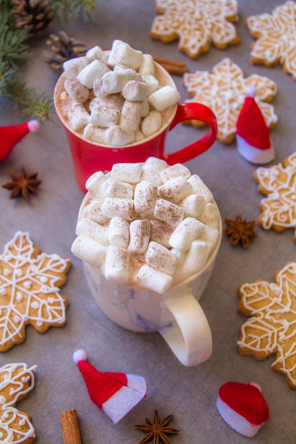 Two hot chocolate cups and marshmallows , against grey background & Christmas composition with Snowflake gingerbread cookies royalty free stock photos