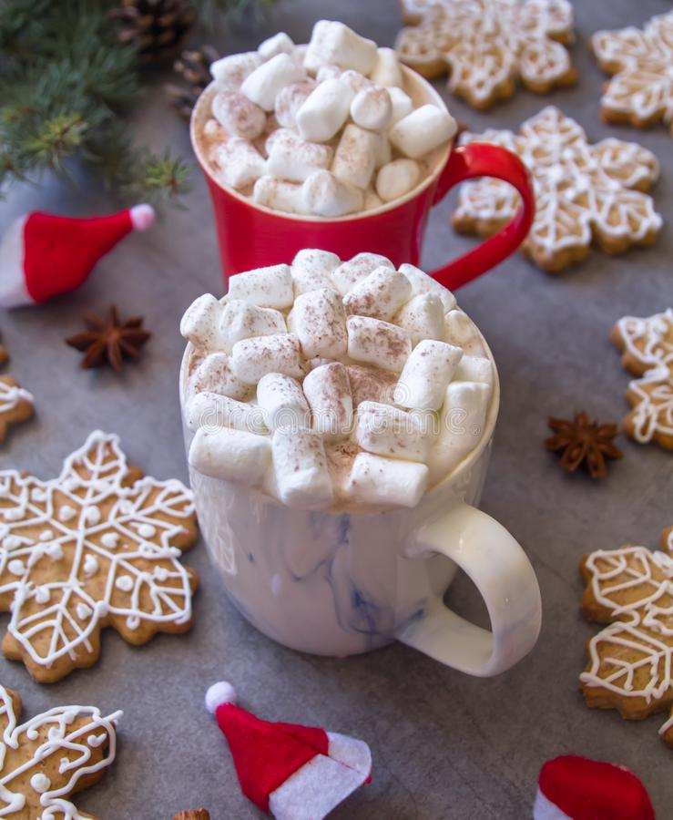 Two hot chocolate cups and marshmallows , against grey background & Christmas composition with Snowflake gingerbread cookies royalty free stock photo