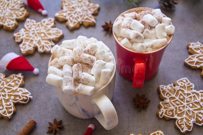 Two hot chocolate cups and marshmallows , against grey background & Christmas composition with Snowflake gingerbread cookies stock photo