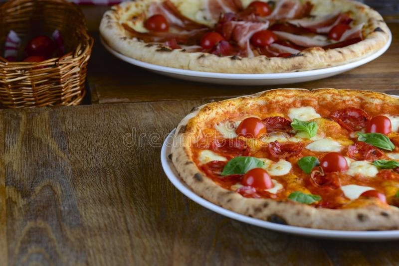 Two hot tasty pizza with pepperoni, prosciutto, mozzarella, cherry tomatoes and basil, served on a dark wooden table for a dinner. royalty free stock photography