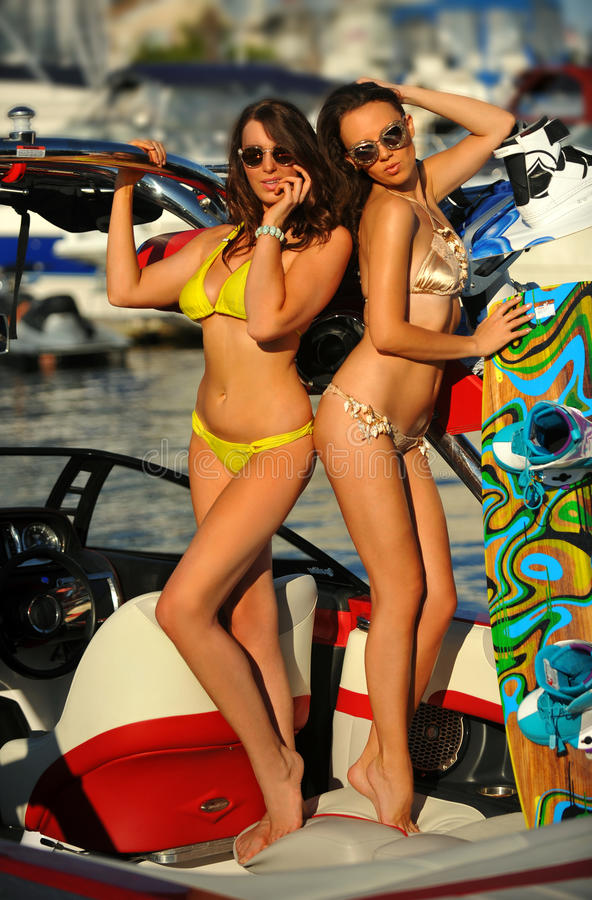 Two hot young bikini models posing on the sport speed-boat stock images