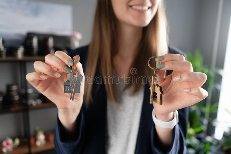 Two house keys in womans hands. Young pretty woman smiles. Modern light lobby interior. Real estate, hypothec, moving stock photo