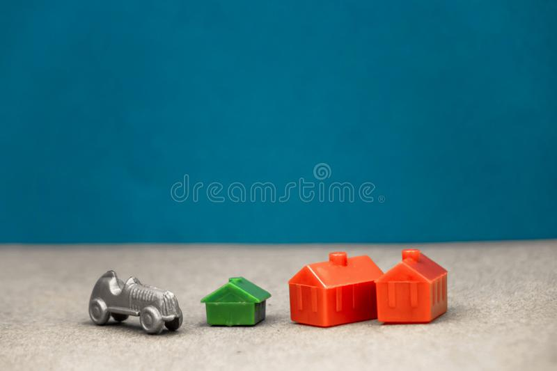 Two houses are red and one is green with a gray car standing next to it on a blue background stock photo