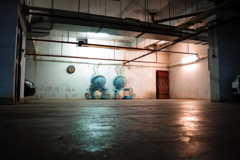 Two huge blue bunny figurines laying on the ground in a dark, spooky underground garage, with grungy water pipes on the ceiling stock images