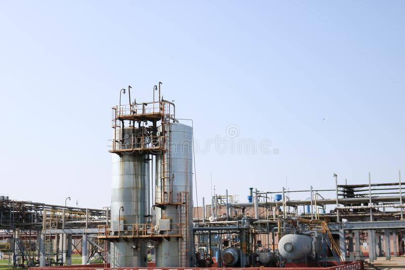 Two huge high metal tanks, barrels, heat exchanging equipment, pumps, pipes, pipeline estocades with valves at an oil refinery, pe. Trochemical, chemical plant stock photo