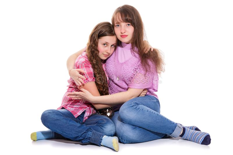 Two hugging sisters. Isolation on a white background royalty free stock image