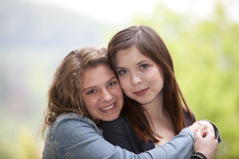 Two hugging teenage girls stock photos