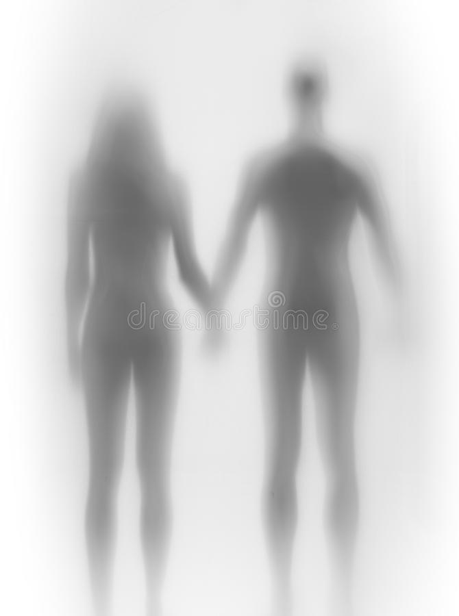 Lover couple stands together, hold each others hand, body silhouette. Two human body shape can be seen from behind. A female and a male together stock photography