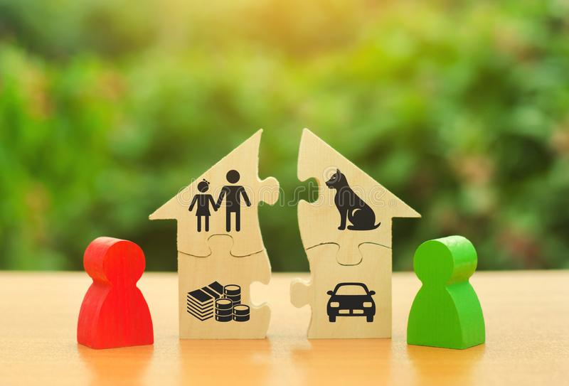 Two human figures divide the house among themselves. Divorce concept. Execution of the posthumous will. Disputes over division. Process of real estate and stock photo