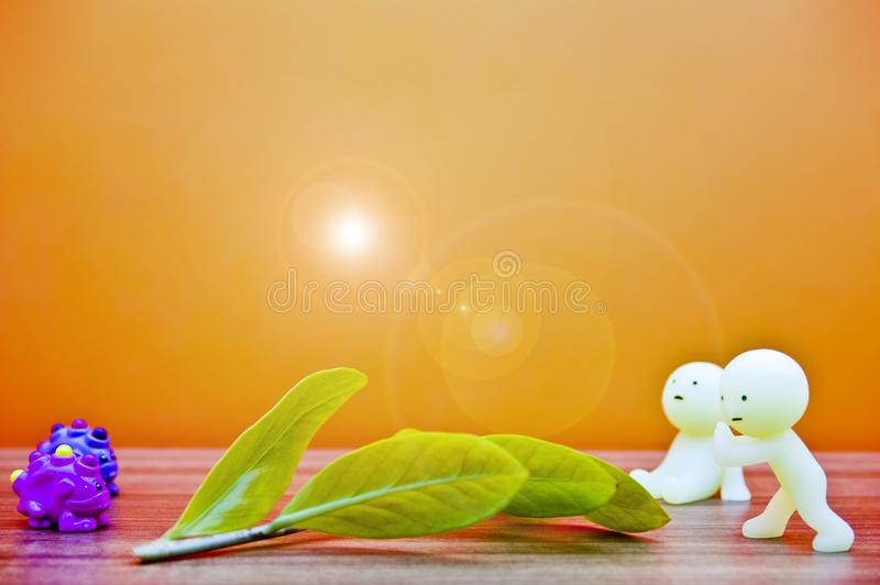 Two human model puppets, two animal puppets, Tree leaf, sun and orange background. royalty free stock images