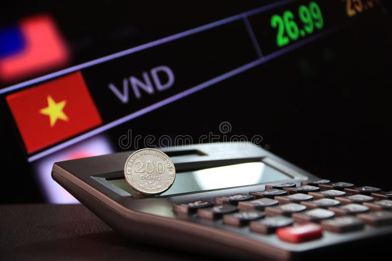Two hundred Vietnam coin on reverse VND on black calculator and black floor with digital board of currency exchange money royalty free stock image