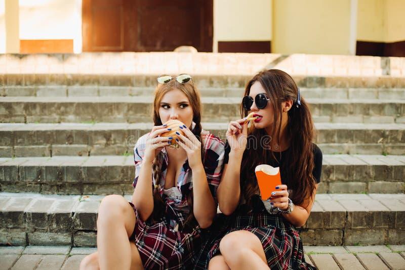 Hungry hipster girls eating hamburger and potatoes. royalty free stock photography