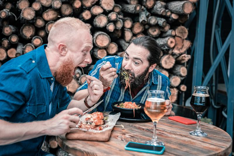 Two hungry men feeling good while having tasty dinner. Tasty dinner. Two bearded hungry men feeling very good and satisfied while having tasty dinner royalty free stock image