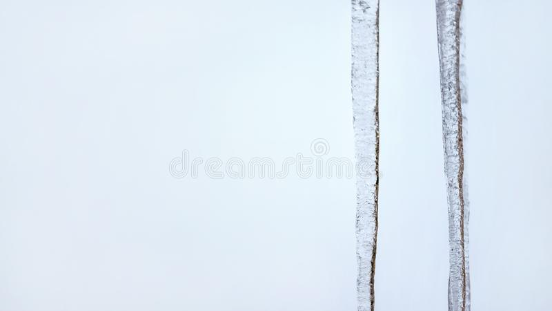 Two icicles with light blue overcast sky in background. Wide banner, space for text left side stock image