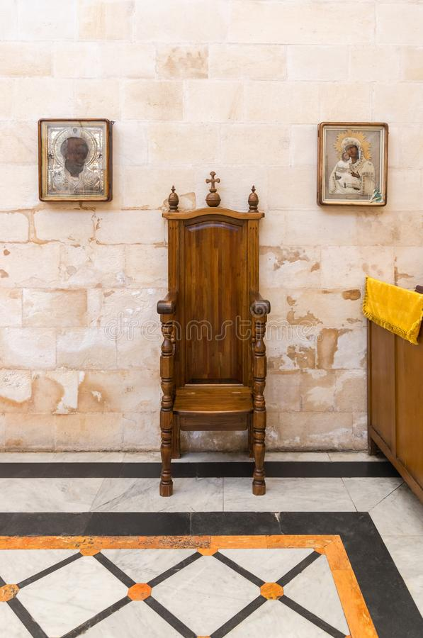 Two icons hang on the wall on the sides of the decorative wooden throne in Alexander Nevsky church in Jerusalem, Israel. Jerusalem, Israel, November 17, 2018 stock photo