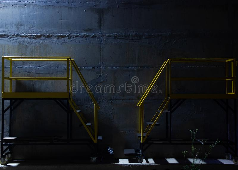 Two identical industrial ladders near a concrete wall. Two identical industrial ladders used in a fruit packaging facility. The concrete wall high lights the royalty free stock image