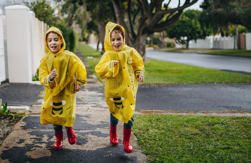 Two identical twin sisters in raincoats stock photography