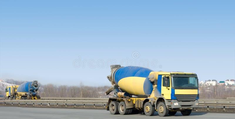 Two identical  yellow concrete mixer trucks