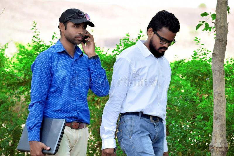 Two businessman using mobile with laptop in the park. Two Indian businessman using mobile with laptop in the park stock photography