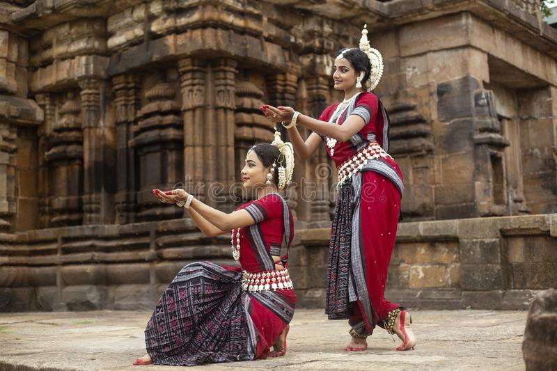 Two Indian classical odissi dancers Pushpanjali in front of Mukteshvara Temple,Bhubaneswar, Odisha, India. Two Indian classical odissi dancers striking a pose in stock images
