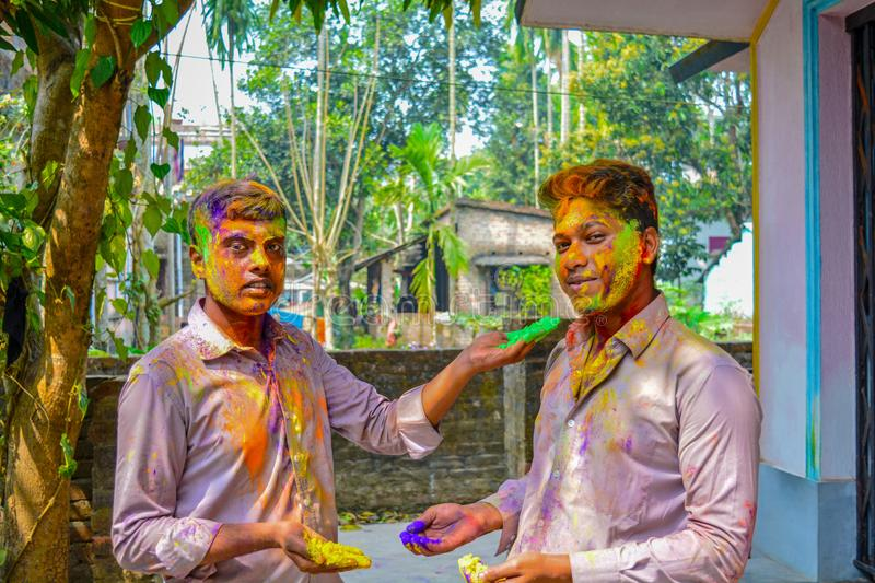 Portrait of two Indian friends are coloring each other during the Holi festival. royalty free stock images