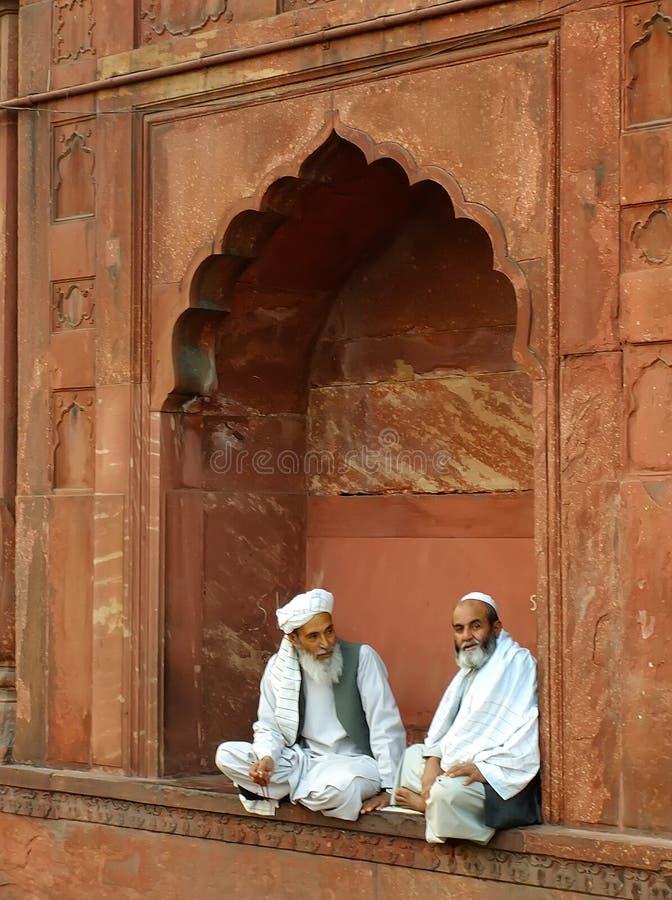 Two indian men sitting at Jama Masjid, Delhi stock image