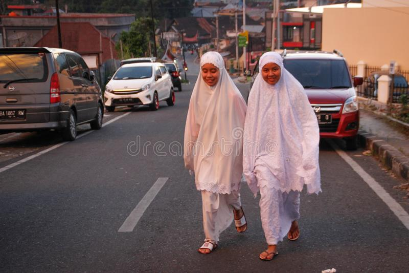 Two Indonesian girls are walking on a city street in white clothes and hijab royalty free stock image