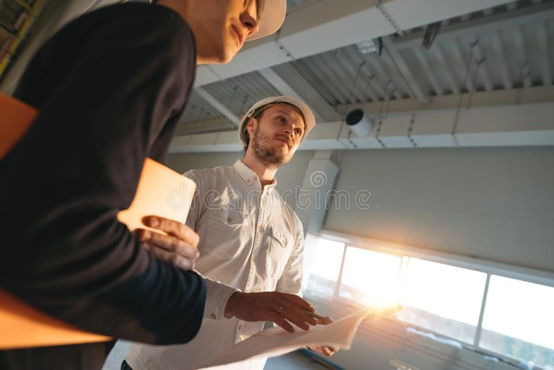 Two industrial engineers wearing safety hard hat have meeting on commercial building structure stock photo