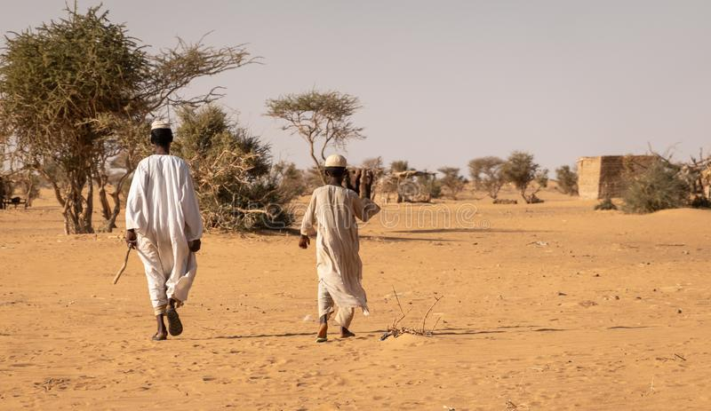 Two inhabitants of the desert in Kaftan on the way back to their mud hut in the desert royalty free stock images
