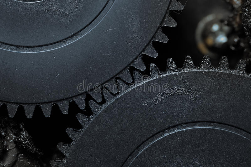 Two interlocked dirty gearwheels. In action royalty free stock images